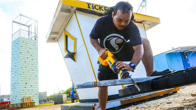 Pitshop Rentals' employee Darr Naputi saws a piece of lumber to help stabilize the ticket booth he and others were installing at the Liberation carnival grounds in Tiyan on June 8. Pitshop vendor Robert Pitter says the structure will be used to sell tickets for their attractions, which includes a zipline, air jumper, and a new rock climbing tower the company will be operating at the site.