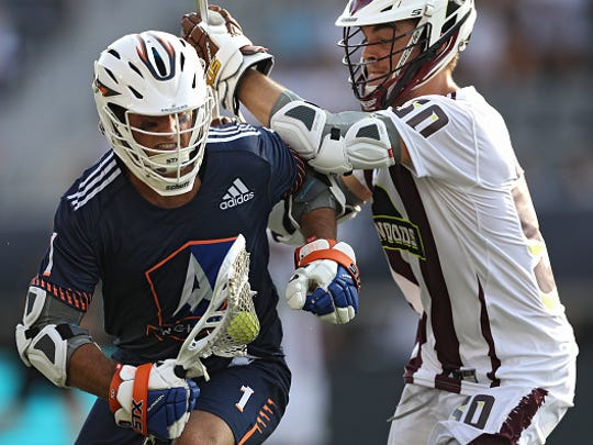 Marcus Holman (1) of the Archers is checked by Ryder Garnsey (50) of the Redwoods during a Premier Lacrosse League game in Washington, D.C., on July 6, 2019.