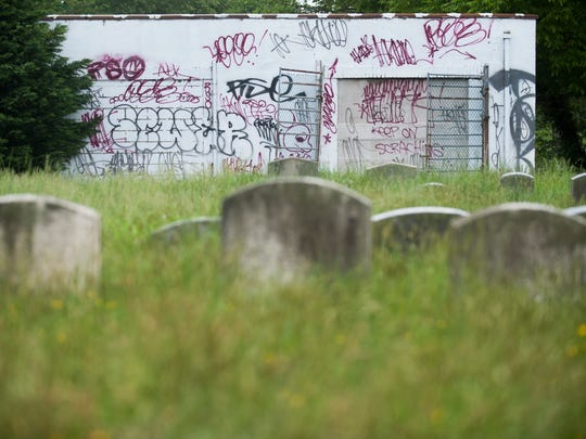 Graffiti covers a wall in the Evergreen Cemetery in Camden.  The cemetery is overgrown and littered with trash and debris.