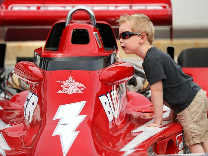 Four-year-old Jacob Speer of Greenwood takes a peek inside a 1978 Romlin Lightning vintage race car on display in pit lane during Community Day at the Indianapolis Motor Speedway on Wednesday, May 21, 2014.