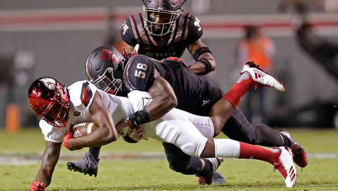 Louisville's Corey Reed runs the ball while North Carolina State's Airius Moore (58) and Tim Kidd-Glass (34) move in for the tackle during the first half of an NCAA college football game in Raleigh, N.C., Thursday, Oct. 5, 2017. (AP Photo/Gerry Broome)