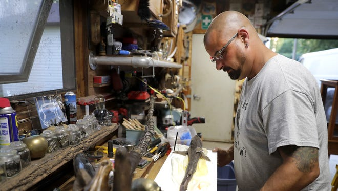 Scott Watzlawick works on pinning down a dogfish shark that he plans to mummify and incorporate into an art piece at his home workshop in Appleton.