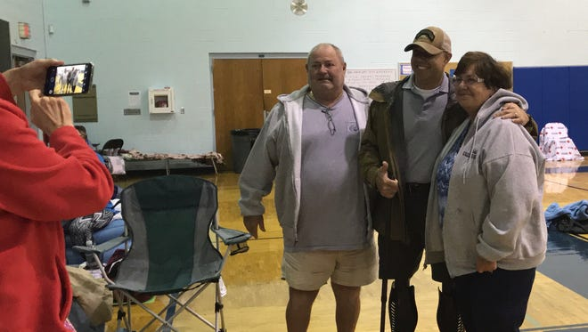 Stuart residents Bob and Joan Marriott pose with Rep. Brian Mast Sunday at the Hidden Oaks Middle School shelter.