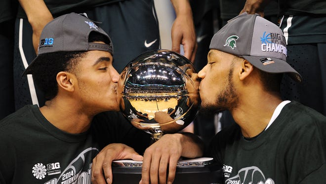 Michigan State guard Gary Harris, left, and forward Adreian Payne kiss the championship trophy after beating Michigan to win the Big Ten Basketball Tournament inside Bankers Life Fieldhouse, Sunday, March 16, 2014, in Indianapolis. Michigan State won the game 69-55.