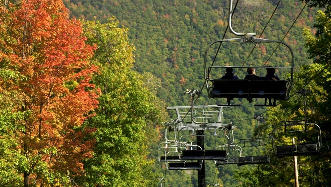 People enjoy the annual Fall Sky Rides at Bristol Mountain in South Bristol.  Carlos Ortiz/FILE PHOTO -  -Text: People enjoy the Sky Rides (Comet Express) at Bristol Mountain on Saturday. The foliage seems to be changing colors a little bit earlier this year, and for $6 to $7 per person the 20 minute chairlift ride is a festival for the senses. Once at the top of the mountain, some trails await to be hiked before returning to the bottom with the chairlift. September 29 2001. Reporter Sheila Rayam. (Democrat & Chronicle, Staff Photo by Carlos Ortiz, 092901).