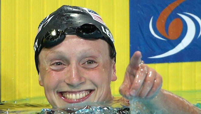 Katie Ledecky of the USA acknowledges the crowd after setting a world record in the 1,500 freestyle.
