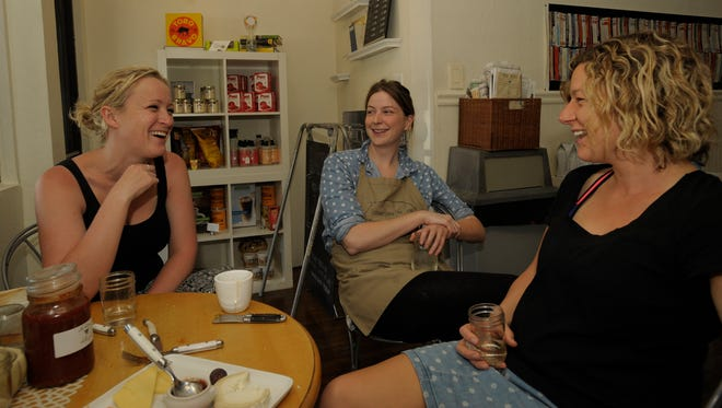 Tilly Plate, left, and Liz Ouslinis, right, both of Adelaide, Australia, visit with Charcuterie owner, Catherine Heaney. Tilly brought her homemade willy dale farm chilli jam from Australia for Catherine to taste.