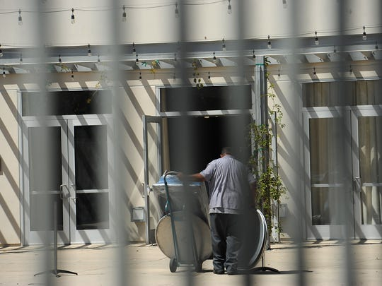A worker on Tuesday removes tables and equipment used for a weekend event in the courtyard of the Museum of Ventura County in Ventura.