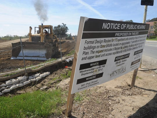 A sign announces a public hearing for an apartment project planned in Ventura.