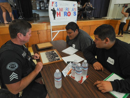 Ventura Police Sgt. Jerry Foreman shows Pacific High School students Jonathan Navarro and Alfredo Garcia (right) photos from when he served in the Navy as they interview him for the school's Voices for Veterans project.