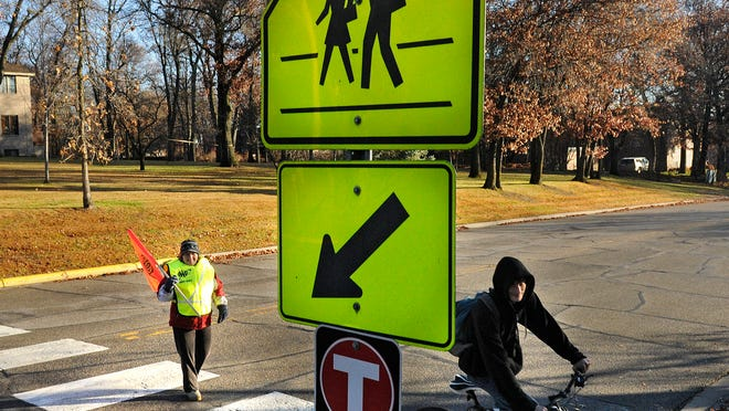 Safe Routes to School plans are taking hold in Sartell, and the idea is also part of Benton County efforts under the Statewide Health Improvement Program. In this November file photo, crossing guard Crystal Erickson helps a student cross Seventh Street North in Sartell.