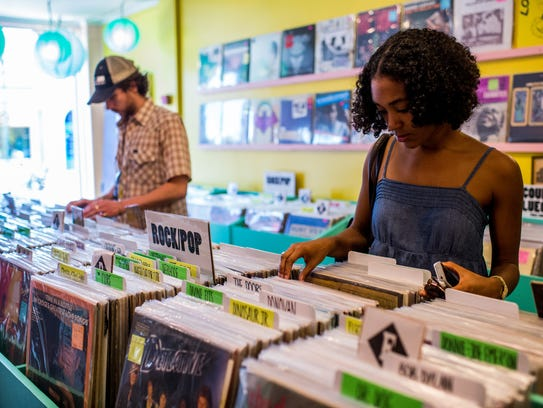 Olivia Chatman browses through a shelf of vinyl records