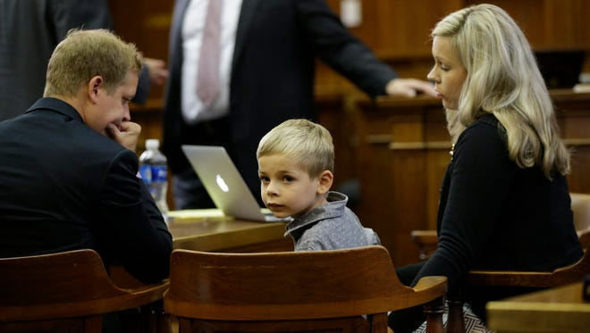 Mel Russell, 6, sits between his parents, Nicole and Melbourne III, in the Milwaukee County Courthouse in September. As a newborn, Mel was not diagnosed with the metabolic condition that later caused him to have a stroke and suffer brain damage. Protocol and cutoffs used by the Wisconsin State Lab led to Mel's condition being missed. It's nearly impossible to sue a state lab. Mel's parents filed a medical malpractice lawsuit against his pediatrician, alleging that she could have done more to make sure Mel was diagnosed.