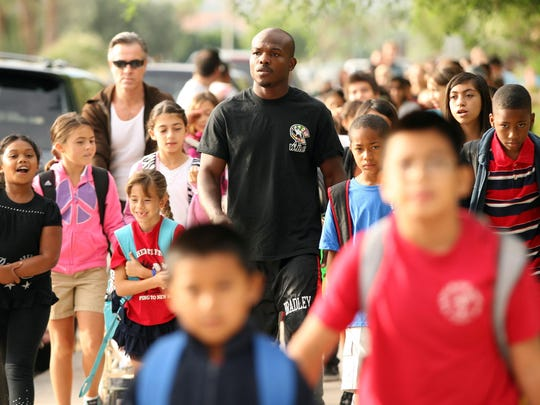 """Professional boxer Timothy """"Desert Storm"""" Bradley (center) walks with Katherine Finchy Elementary School students, parents, and teachers from the Palm Springs Convention Center to the school in Palm Springs, Calif. during the International Walk to School day in 2011."""