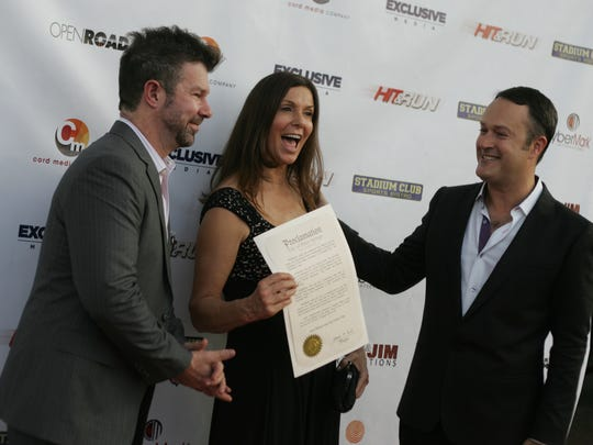 Producers Kim Waltrip and Jim Casey (left) are given a city proclamation by Palm Springs city councilman Paul Lewin at the Regal Cinemas Stadium 9 Palm Springs in 2012.