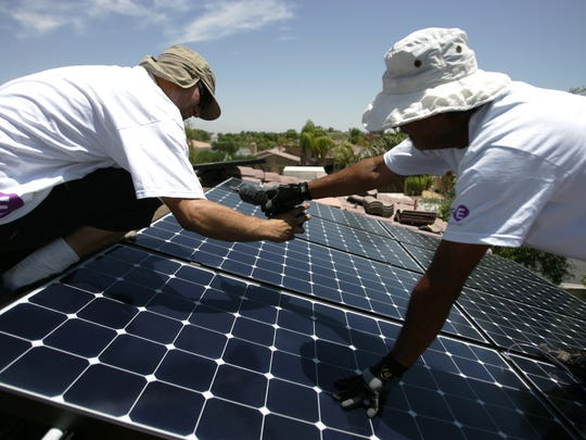 Solar panel installers with Hot Purple Energy (Paul Lemon, right, of Morongo Valley and Phillip Wittwer) bolt on solar panels in a 54 panel home installation job in Rancho Mirage, Wednesday, May 23, 2012. (Richard Lui The Desert Sun)