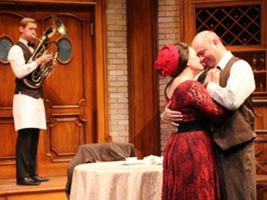 "New waiter Antoine (Daniel Burns) serenades Miss Berger (Katherine Puma) and Victor (Jim VanValen) in a poignant scene in Riverside Theatre's production of ""An Empty Plate in the Café du Grand Boeuf."""