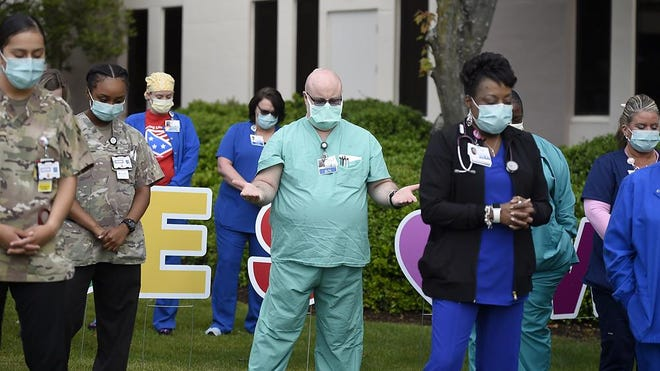 Nurses stand and pray during the Blessing of the Hands Ceremony at outside Doctors Hospital in Augusta, Ga., Friday morning May 8, 2020.