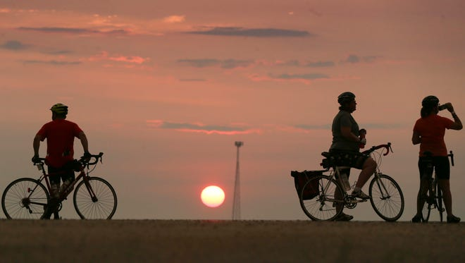 Riders stop to admire the sunrise as they leave Denison, Iowa, Monday, July 23, 2018, as RAGBRAI 2018 heads to the overnight town of Jefferson.