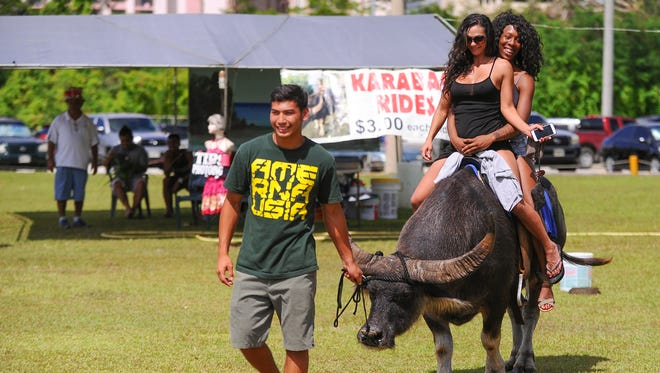 In this June 12, 2016, file photo, two women take a carabao ride at the 28th Annual Guam Micronesia Island Fair at the Gov. Joseph Flores Memorial Park in Tumon.