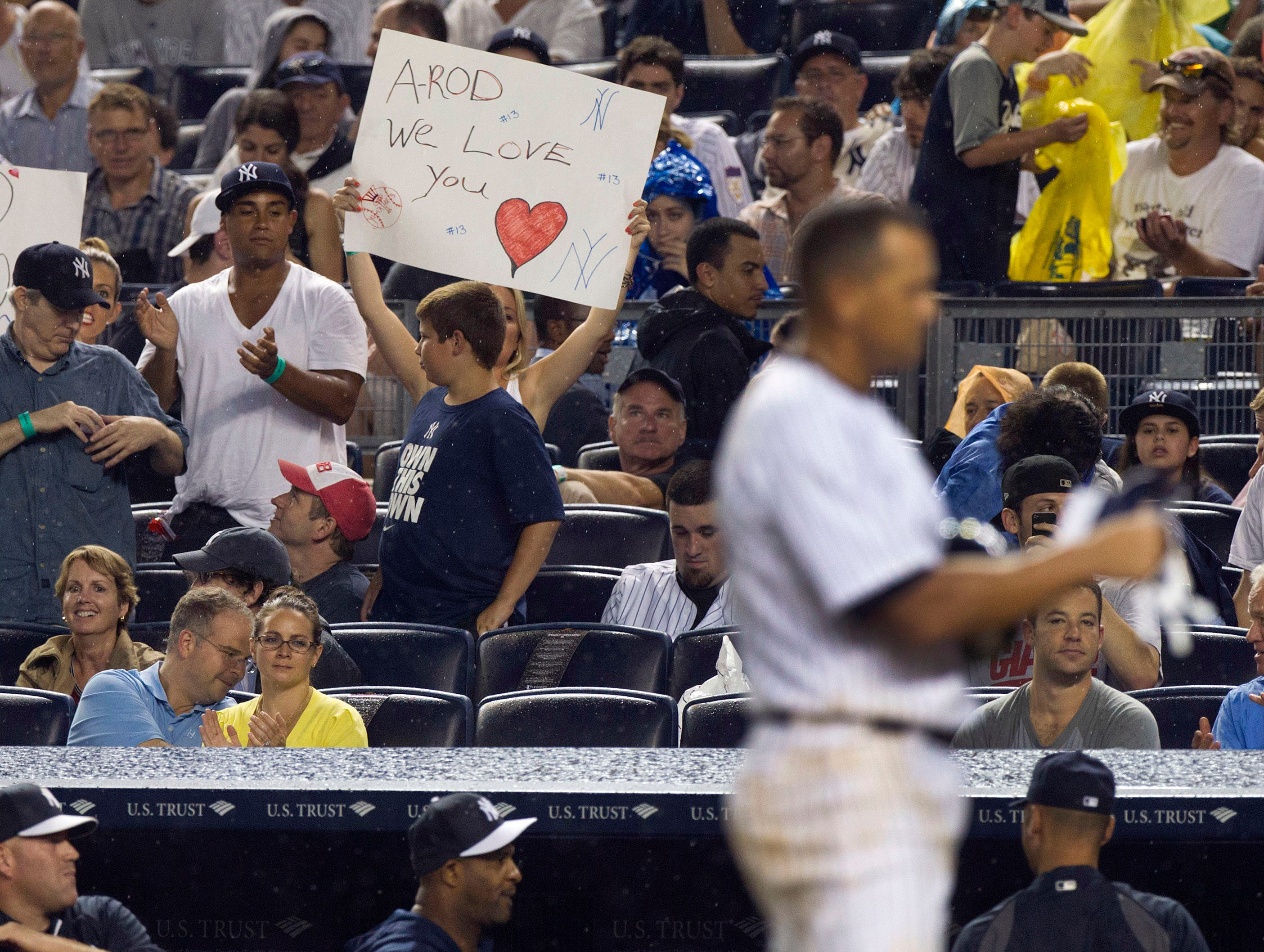 Fans hold signs as New York Yankees third baseman Alex Rodriguez strikes out during the first inning against the Detroit Tigers at Yankee Stadium.