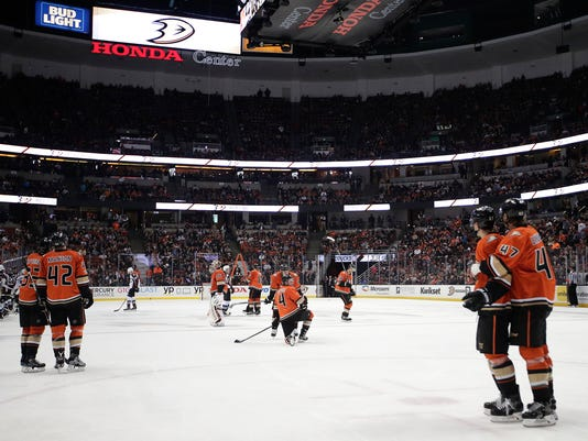 Players wait around on the ice while workers look for a replacement plexiglass piece during the second period of an NHL hockey game between the Anaheim Ducks and the Colorado Avalanche Thursday, Jan. 19, 2017, in Anaheim, Calif. (AP Photo/Jae C. Hong)