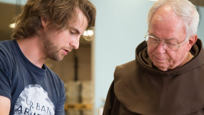 Bret Kollmann Baker (left), Urban Artifact's chief of operations, shows Fr. Carl Langenderfer the grains used in their new brew.