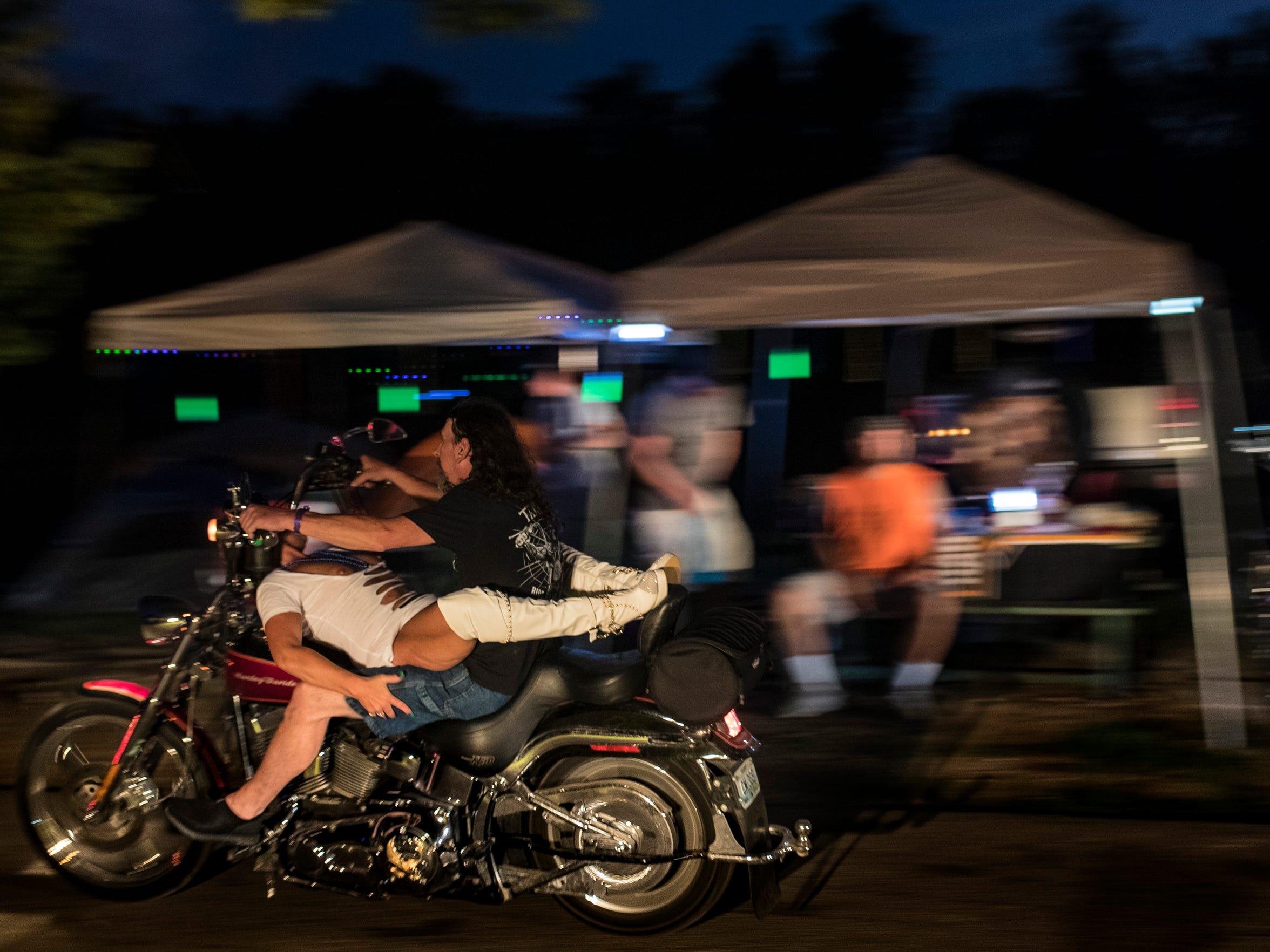 A biker passes by campsites as he is straddled by a