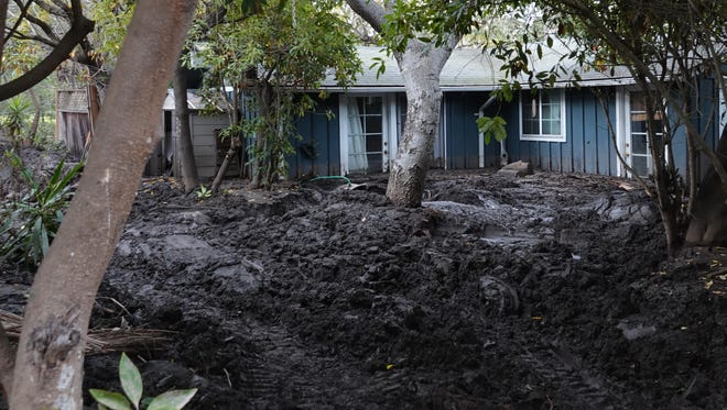 A weather system headed to toward Ventura County Monday night could possibly bring thunderstorms that pose a risk to Thomas Fire burn areas. In this Jan. 19 photo, a house on Depot Road in Montecito remained mired in mud ten days after fatal debris flows there inundated the community.