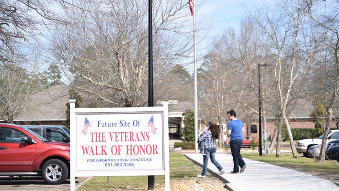 A family walks along the newly paved Veterans Walk of Honor in Petal. The walkway leads to the city's memorial to veterans of all branches of the military.