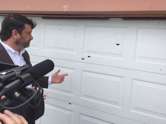 Attorney John Phillips points to bullet holes in the garage door of the Hill home on Wednesday, January 20, 2016. Gregory Hill Jr. was killed in January 2014 after a confrontation with St. Lucie County deputies at his home in the 1500 block of Avenue Q in Fort Pierce.