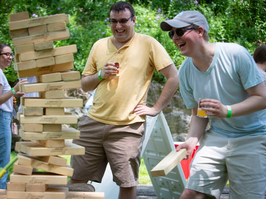 Steven Punto of Parsippany, center, reacts after Kevin Kieran of Randolph pulls the final block that collapsed the pile during the 2nd Annual Boonton Main Street Rock & Brew Festival on Saturday, June 2 2018. Jersey Club Sports provided games like this for the festival