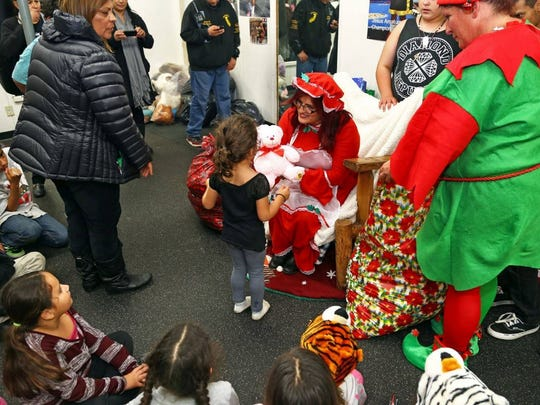 "Debbie Aguilar, founder of A Time for Grieving and Healing, gives out presents at a past ""Christmas in the Park."""