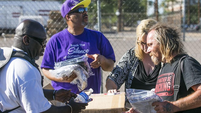 Robert Boyd (in purple), his wife Lucinda Boyd (in black) and Robert Bowden (left in white) hand out water, nutrition bars and shirts near Central Arizona Shelter Services in downtown Phoenix, AZ on July 9, 2015. Once trapped in a spiral of crime, Robert Boyd and Bowden now seek to help others.