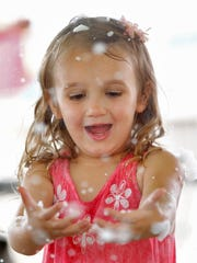 Madelyn Hotaling 4, of Endicott, has fun playing in foam as Mikayla Write shoots pretend snow while being entertained by Johnny Only during Ava's Little Heroes benefit at Animal Adventure in Harpursville on Sunday, August 14, 2016.