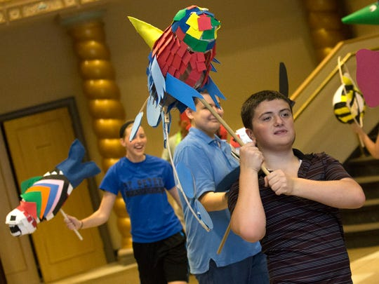 Children from the Integrated Theater Company  display puppets they made to parents and relatives in the lobby of the Renaissance Theatre on Thursday. The program, in collaboration with St. Peter's Catholic Church, helps children with autism.
