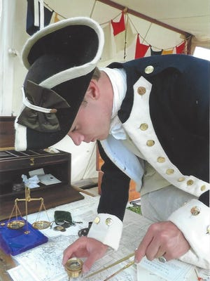 Bryan Andrews stands at his charting table, in his Continental Navy Uniform, doing a demonstration of how charts and navigational instruments were used in 18th century navigation.