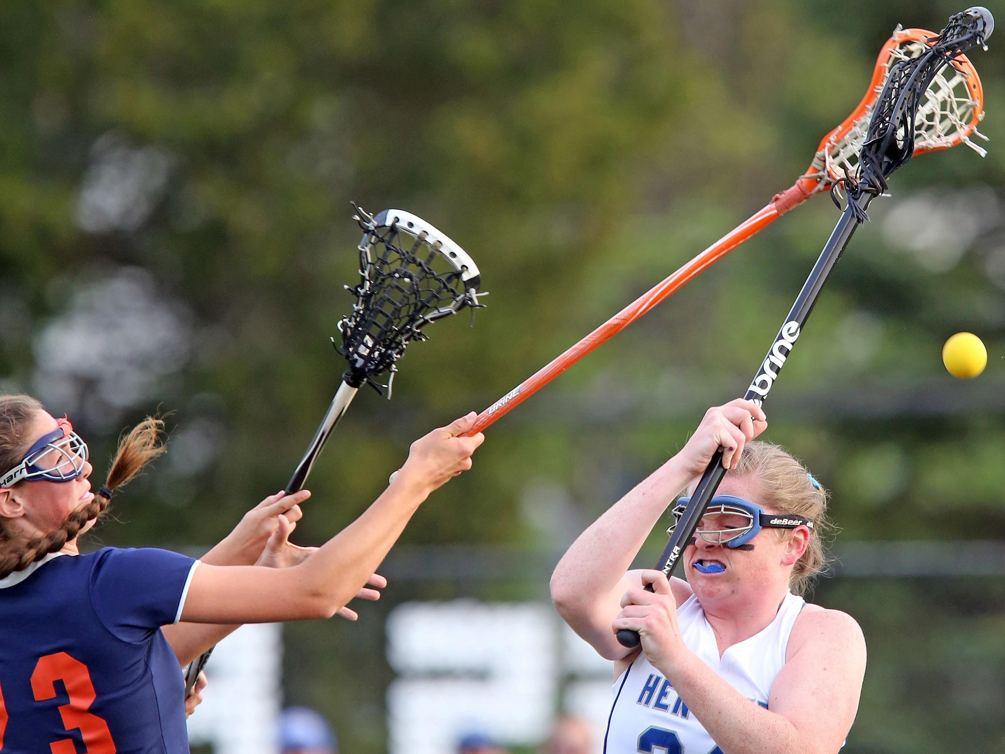Briarcliff's Kelly O'Donnell (23) knocks the ball away from Hendrick Hudson's Jill Reiner (24) during girls lacrosse game at Hendrick Hudson High School in Montrose May 11, 2016.