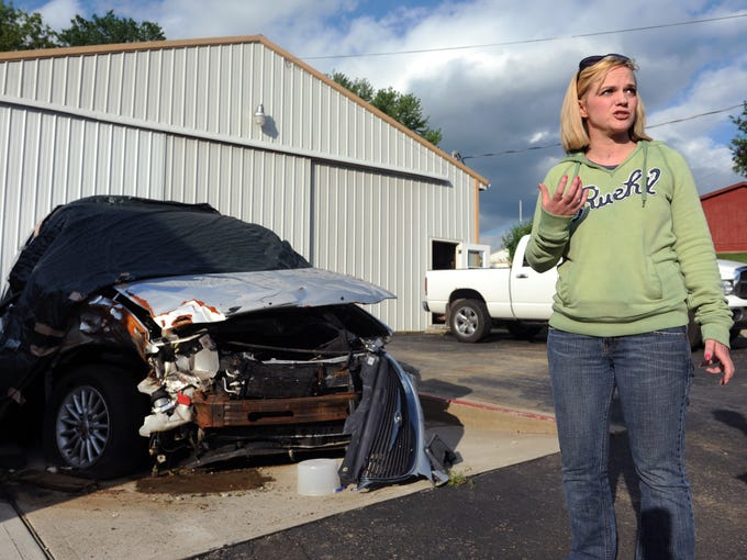 Stephanie Latier stands next to the remains of her