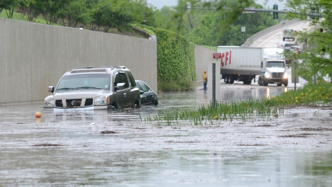 Cars are left stranded on the exit ramp between Jackson and Elliott streets Thursday afternoon as the underpass flooded.