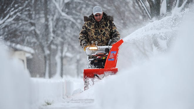 Harvey Wollman, of Sioux Falls, uses a snow blower to clear the sidewalk near his house during the first snow of the season Friday, Nov. 20, 2015, in Sioux Falls, S.D. (Joe Ahlquist/The Argus Leader via AP)