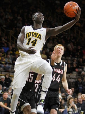 Iowa's Peter Jok (14) goes to the basket in front of Omaha's Tre'Shawn Thurman (15) and Mitch Hahn (44) during a game in December.