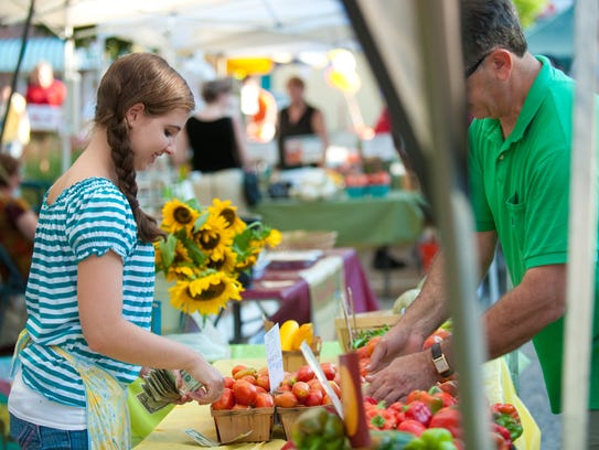 A vendor sells produce at the Westmont Farmers Market.