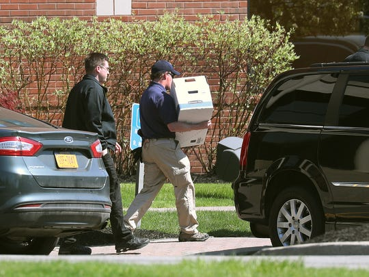 Federal agents leave the offices of Morgan Management LLC in Perinton as they conducted a raid and collected items from the building for an investigation.