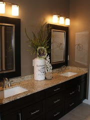 Dark maple cabinets with granite countertop and undermount sinks.