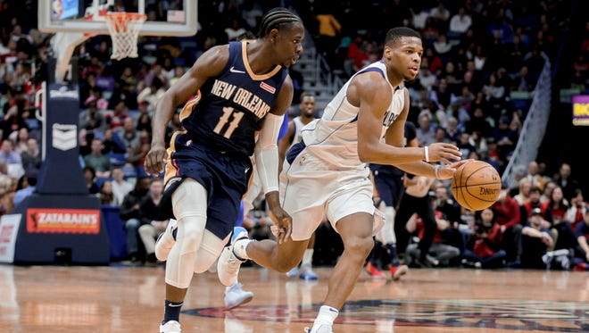 Dallas Mavericks guard Dennis Smith Jr. (right) drives past New Orleans Pelicans guard Jrue Holiday (11) during the first quarter at the Smoothie King Center.
