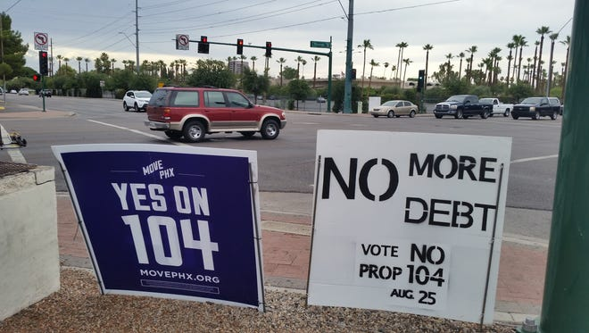 This Saturday, July 18, 2015, photo shows campaign signs for, left, and against an initiative to expand Phoenix's transportation systems at an intersection in Phoenix. With city elections in Phoenix next month and 2016 races around the corner, Arizona regulators are warning people that they might need to pull up stakes on the many campaign signs on lawns and street corners.