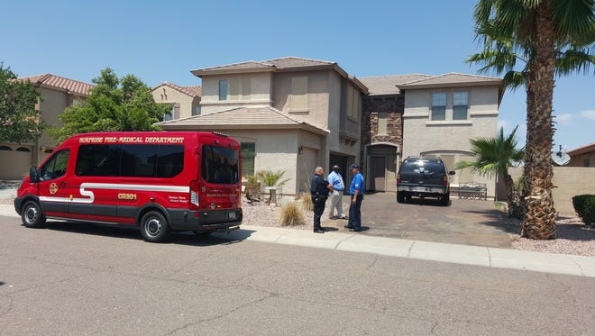 Surprise emergency crews stand outside a home where a woman was found unresponsive in her pool.