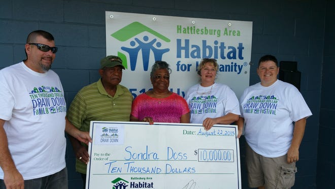 Officials from the Hattiesburg Area Habitat for Humanity present Sondra Dpss with the $10K check.