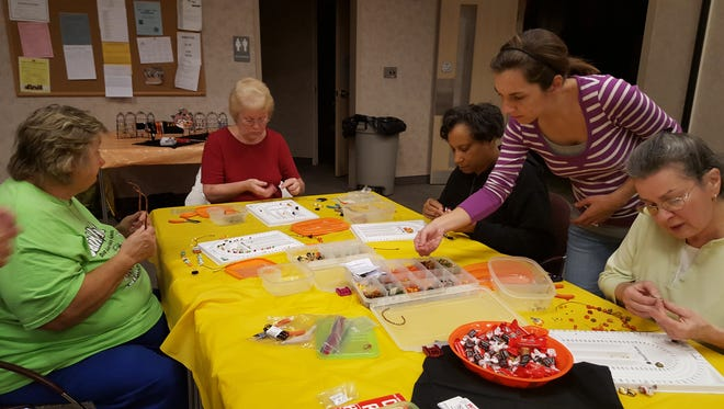 Participants in Franklin Township Library's fall jewelry design class make various festive items with a Halloween theme.